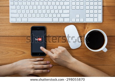 CHIANGMAI,THAILAND - JULY 17, 2015:Brand new Apple iPhone with YouTube app on the screen lying on desk with headphones. YouTube is the popular online video-sharing website, - stock photo