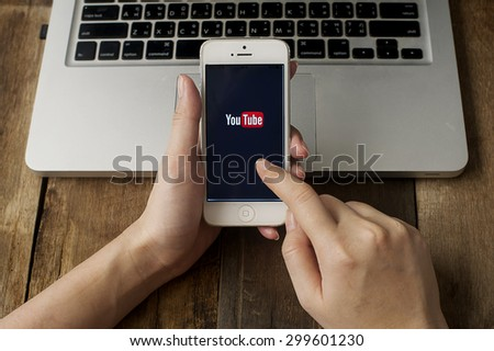 CHIANGMAI, THAILAND -JULY 25, 2015:Brand new Apple iPhone with YouTube app on the screen lying on desk with headphones.  - stock photo