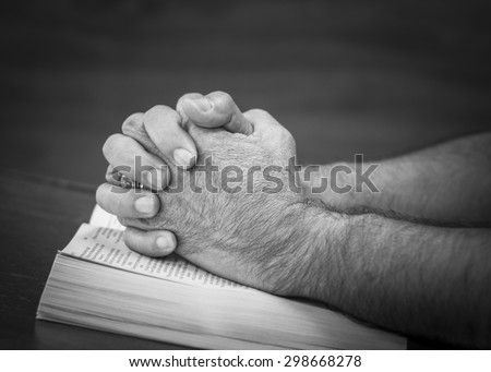 CHIANGMAI, THAILAND - July 22, 2015. Praying hands of a man on the open  bible (New International  Version) christian believe that  the bible is the word of God and try to reading the bible everyday. - stock photo