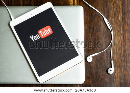 CHIANGMAI, THAILAND -JUNE 05, 2015:Brand new Apple iPad with YouTube app on the screen lying on desk with headphones. - stock photo