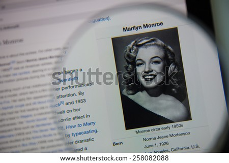 CHIANGMAI, THAILAND - March 5, 2015: Photo of Wikipedia article page of marilyn monroe on a ipad monitor screen through a magnifying glass. - stock photo