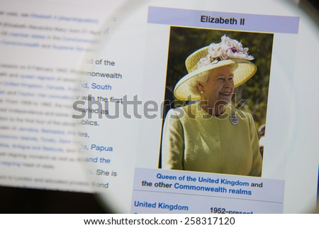 CHIANGMAI, THAILAND - March 5, 2015: Photo of Wikipedia article page of Queen Elizabeth II on a ipad monitor screen through a magnifying glass. - stock photo