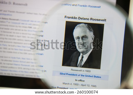 CHIANGMAI, THAILAND - March 5, 2015: Photo of Wikipedia article pageof Franklin D. Roosevelt on a ipad monitor screen through a magnifying glass. - stock photo