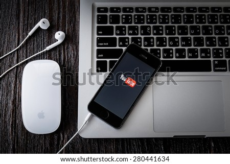 CHIANGMAI, THAILAND -MAY 22, 2015:Brand new Apple iPhone with YouTube app on the screen lying on desk with headphones. - stock photo