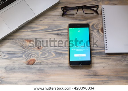 """CHIANGMAI,THAILAND - MAY 14 ,2016 :iPhone 6 plus open Twitter application on rustic table,Twitter is an online social networking and microblogging service that enables users to send and read """"tweets""""  - stock photo"""