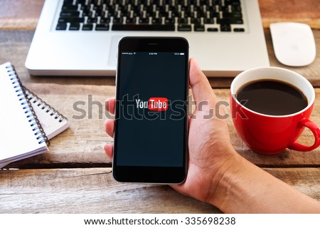 CHIANGMAI, THAILAND -NOV 05, 2015:Brand new Apple iPhone with YouTube app on the screen lying on desk with headphones.  - stock photo