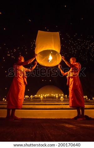 CHIANGMAI, THAILAND - NOV 16: Buddhist monks release sky lantern to worship Buddha's relics during Yi Peng festival on November 16, 2013 in Chiangmai, Thailand - stock photo