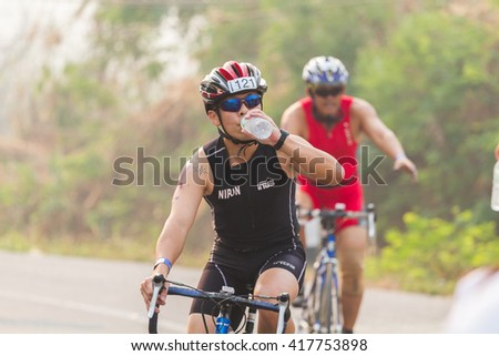 CHIANGRAI -APRIL 3 : Triathlon athletes are drinking water form bottle during cycling in the tournament Golden Triangle International Triathlon. On April 3, 2016 at Chiang Saen, Chiang Rai, Thailand.