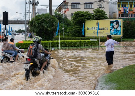 CHIANGRAI, THAILAND 6 AUGUST 2015, Flooding in Chiangrai in front of MAE FAH LUANG UNIVERSITY, unidentify officer help with the bad traffic