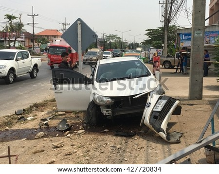 CHIANGRAI, THAILAND - MAY 13th, 2016: White Toyota Vios car wreckage due to bad car accident with officer from insurance company looking over at the car wreck