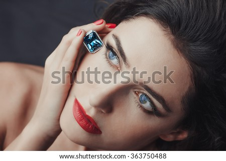 Chic style. Close-up portrait of sensuality beautiful woman model face with fashion make-up, sexy evening red lips makeup and bright red manicure, red lipstick, blue eyes, blue sapphire jewelry ring - stock photo