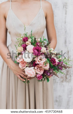 Chic wedding bouquet of peonies and roses in hands of the bride