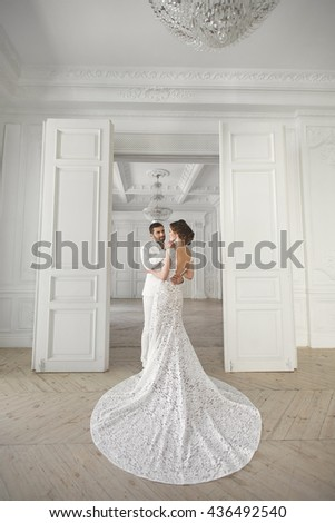 Chic wedding couple groom and bride posing in a white Studio. Happy couple laughing. White dress. White suit. Youth. Wedding. Chandelier. Sofa. The door. - stock photo