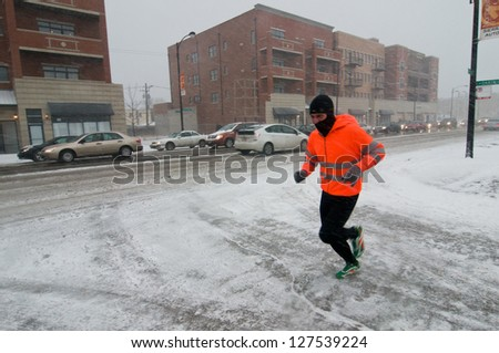 CHICAGO - FEBRUARY 1: A man jogs during a massive winter storm on February 1, 2011 in Chicago. The storm brought as much as 21 inches of snow, making it the third worst blizzard in Chicago history. - stock photo