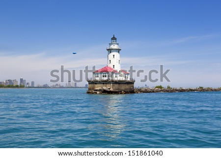 Chicago harbor lighthouse in the summer with city skyline and airship - stock photo