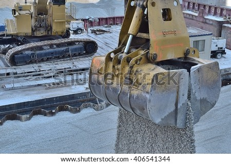 CHICAGO, ILLINOIS - APRIL 15, 2016: Barge excavator releases load of gravel for the Chicago riverwalk expansion project.  - stock photo