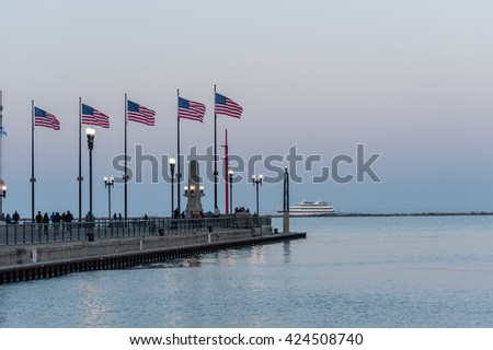 CHICAGO, ILLINOIS - APRIL 17, 2016: Chicago Michigan Lake and Waving USA Flags. Oddysey II yacht in background - stock photo