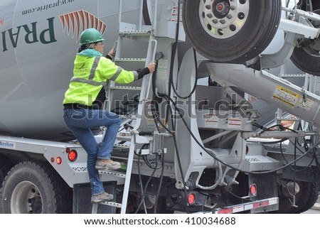 CHICAGO, ILLINOIS - APRIL 23, 2016: Female cement truck worker climbs ladder to clear machinary on top of truck.