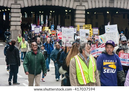 CHICAGO, ILLINOIS - MAY 1, 2016: Hundreds of marchers turned up on May Day to unite around a protest of Trump on the right wing agenda against all workers and immigrants. - stock photo