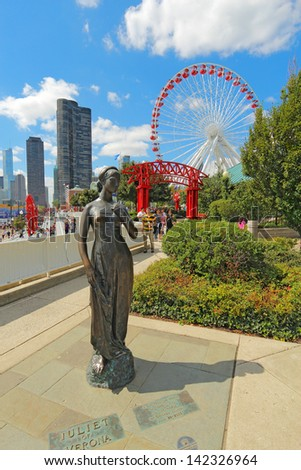 CHICAGO, ILLINOIS - SEPTEMBER 4: Statue, tourists and rides at the Navy Pier in Chicago, Illinois on September 4, 2011. The Pier is a popular destination with many attractions on Lake Michigan. - stock photo