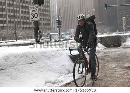 CHICAGO, ILLINOIS/USA-FEBRUARY 4TH: un identified biker rides his bike in Michigan Avenue in winter time on Feb 4th 2014 in Chicago.  - stock photo