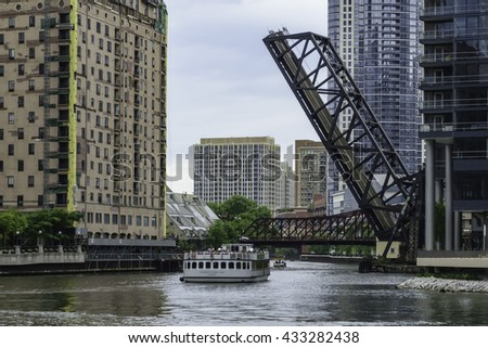 CHICAGO, ILLINOIS/USA - JUNE 4, 2016: A tour boat with sightseers passes under a drawbridge along a branch of the Chicago River on a morning cruise that highlights local history and architecture.