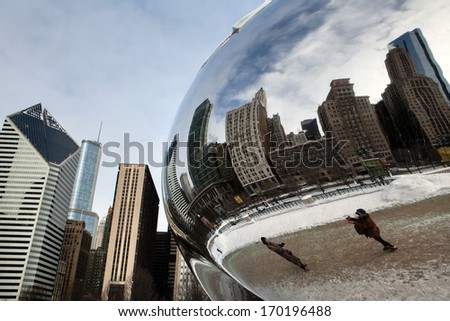 CHICAGO - January 7: The Cloud Gate also known as the Bean covered in snow being viewed by tourists. A famous art piece in AT&T Plaza at Millennium Park, January 7, 2014 in Chicago, Illinois. - stock photo