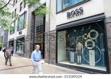 CHICAGO - JUNE 26: People walk past Hugo Boss store at Magnificent Mile on June 26, 2013 in Chicago. The Magnificent Mile is one of most prestigious shopping districts in the United States. - stock photo