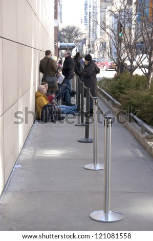 CHICAGO - MARCH 11: People waiting in line hours before Apple's release of the iPad 2 outside of the Michigan Avenue Apple Store on March 11, 2011 in downtown Chicago, Illinois. - stock photo