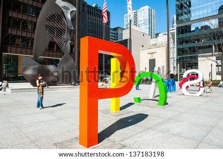 "CHICAGO - MAY 1: A temporary exhibit at Daley Plaza spelling ""Picasso"" stands in front of the original ""The Picasso"" statue in Chicago on May 1, 2013. - stock photo"