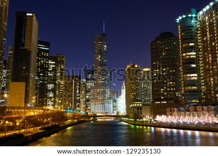 Chicago River with urban skyscrapers and riverwalk at night, IL, USA - stock photo