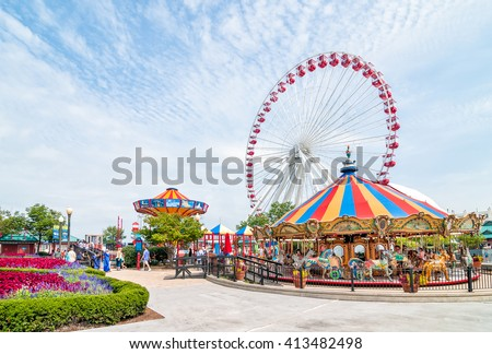 CHICAGO, UNITED STATES - AUGUST 24, 2015: Tourists at the amusement park on Navy Pier. Navy Pier's Ferris wheel, an icon of the Chicago lakefront. - stock photo