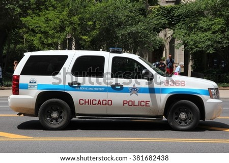 CHICAGO, UNITED STATES - JUNE 28, 2013: People walk past police car in Chicago. Chicago Police Department is one of oldest police forces in the world, dating back to 1837. - stock photo