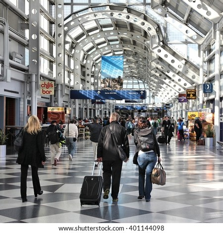 CHICAGO, USA - APRIL 1, 2014: Travelers walk to gates at Chicago O'Hare International Airport in USA. It was the 5th busiest airport in the world with 66,883,271 passengers in 2013. - stock photo