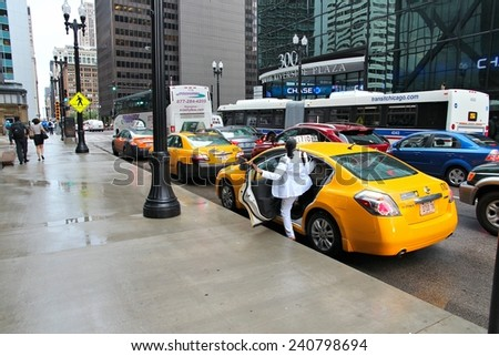 CHICAGO, USA - JUNE 26, 2013: Person catches a yellow cab in Chicago. Chicago is the 3rd most populous US city with 2.7 million residents (8.7 million in its urban area). - stock photo