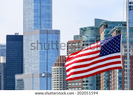 CHICAGO, USA - MAY 24, 2014: The American flag waving in front of a part of the Chicago Skyline including the Trump Tower.