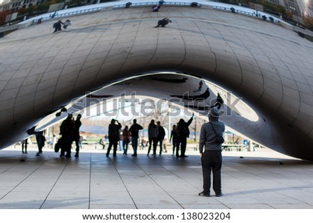 "CHICAGO, USA - NOVEMBER 15: Tourists at the Chicago Cloud Gate sculpture on November 15, 2011. The sculpture is also known as ""The Bean"" because of its shape, a very popular attraction in Chicago. - stock photo"