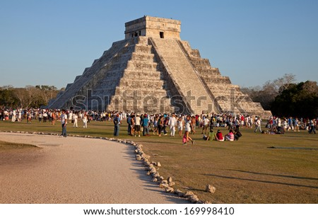 CHICHEN ITZA, MEXICO - MARCH 21: Large Group of tourists visiting the El Castillo temple during sunset on March 21, 2011 in Chichen Itza, Mexico. This temple is one of the landmarks of Mexico. - stock photo