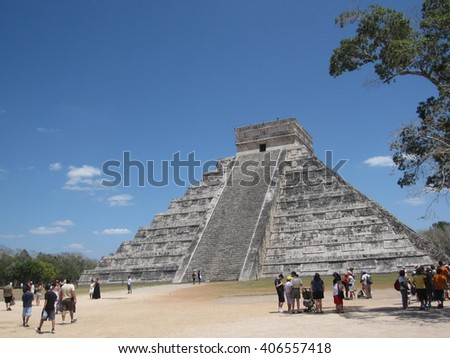Chichen Itza, Mexico on a sunny clear day with tourists milling about the base of the temple - stock photo