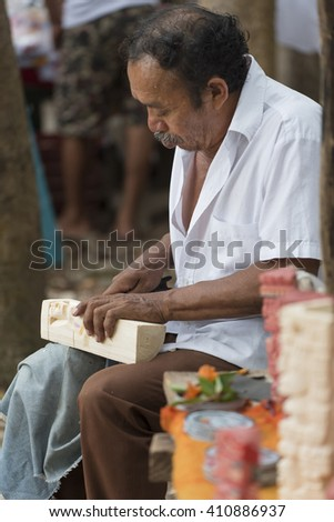 CHICHEN ITZA, YUCATAN, MEXICO MARCH 4, 2016: Local artisan making wood sculptures for sale at tourist attraction site in Chichen Itza.