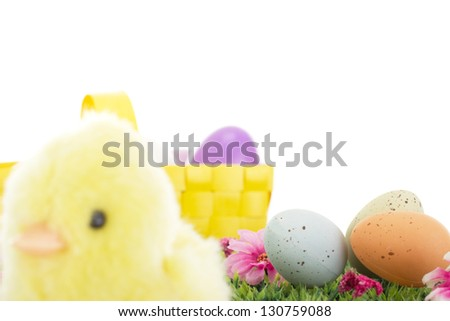 Chick on grass with flowers and easter eggs