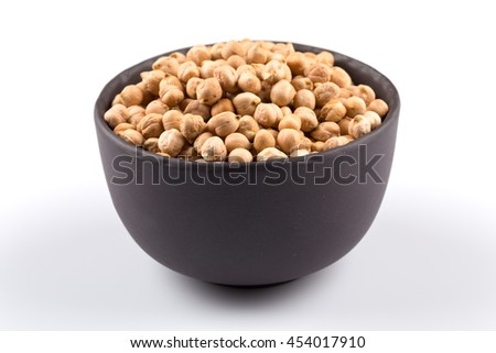 Chick-pea in black bowl. Beans isolated on a white background. Close-up. - stock photo