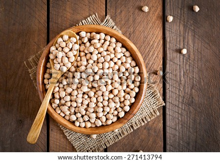 Chick-pea in wooden bowl on wooden background close up. Top view  - stock photo