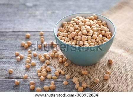 Chick peas in bowl on wooden board - stock photo
