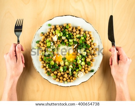 Chick peas with fried eggs, onion and hands - stock photo