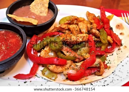 Chicken and bell pepper fajitas on tortilla bread with salsa and beans, on white plate - stock photo
