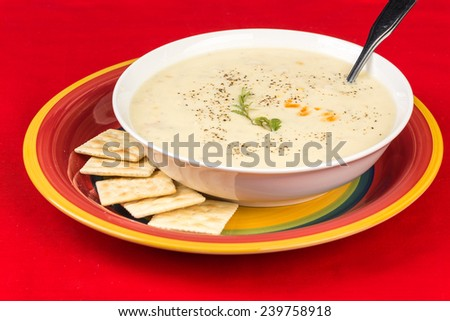 Chicken and Corn Chowder in white bowl on colorful red and yellow plate with saltine crackers against red background with copy space. - stock photo