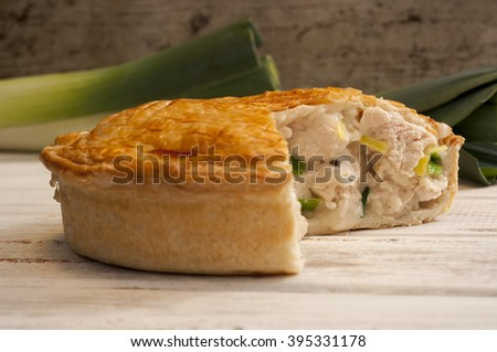 Chicken and leek pie with slice missing on a white wooden surface with fresh leeks in the background. - stock photo