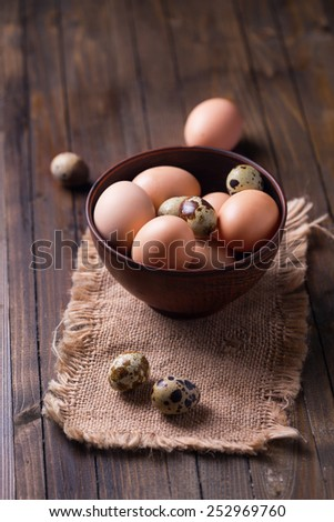 Chicken and quail eggs on wooden background. Selective focus. - stock photo