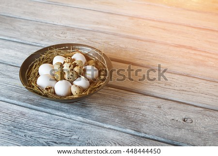 Chicken and quail eggs. Uncooked eggs in a bowl. Protein and cholesterol. Ingredients for tasty omelet. - stock photo